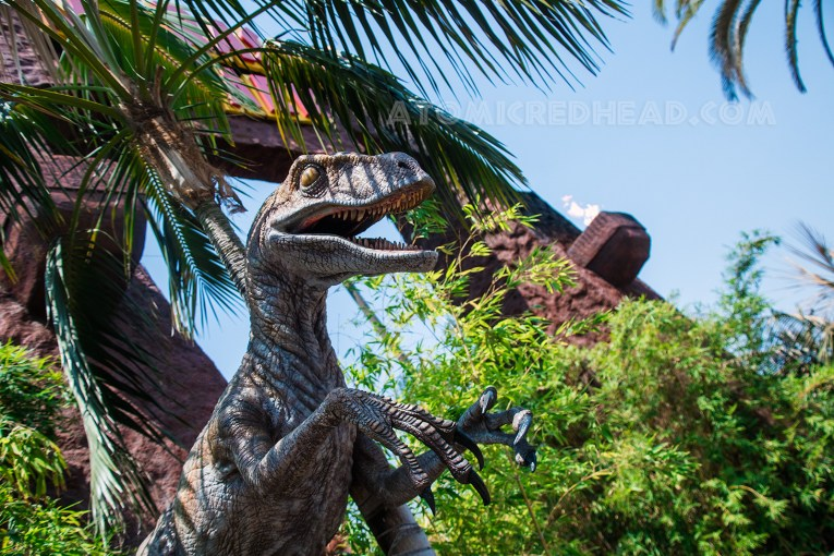 A raptor juts out from the leaves near the entrance to the ride.