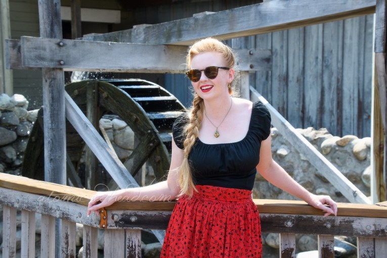 Me wearing a black peasant top, red skirt with a small print of pick axes, shovels, sluice pans, and bags of gold, also wearing black faux-tooled leather shoes.