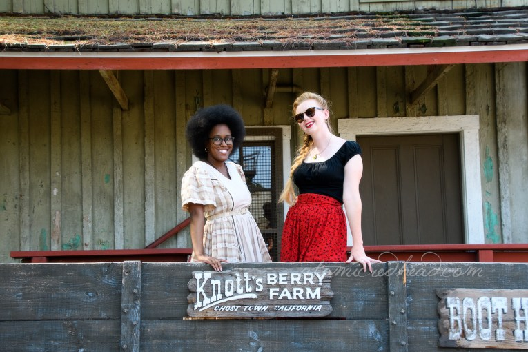"Carla and I in an old wagon that reads ""Knott's Berry Farm Ghost Town California"" on it."