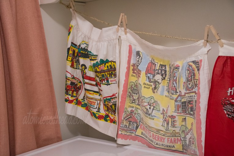 A tighter shot of the two Knott's Berry Farm aprons, each are a color scheme of red, yellow, and black. They feature icons of the park, like the stagecoach, Sad Eye Joe, the Birdcage, and the Saloon.