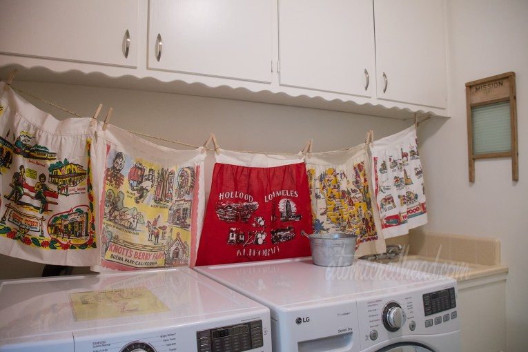 A look at the vintage linens above the washer and dryer. Two Knott's Berry Farm ones, a red one featuring landmarks of Hollywood and Los Angels, another featuring a map of California, and another with icons of Hollywood.