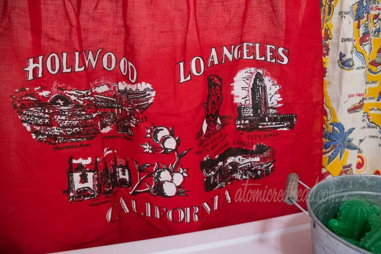 """Close-up of the red apron. Across the top it reads """"Hollywood Los Angeles"""" and across the bottom """"California."""" The illustrations include the Hollywood Bowl, Farmer's Market, Grauman's Theater, Sad Eye Joe of Knott's Berry Farm, Los Angeles City Hall, and Olvera Street."""