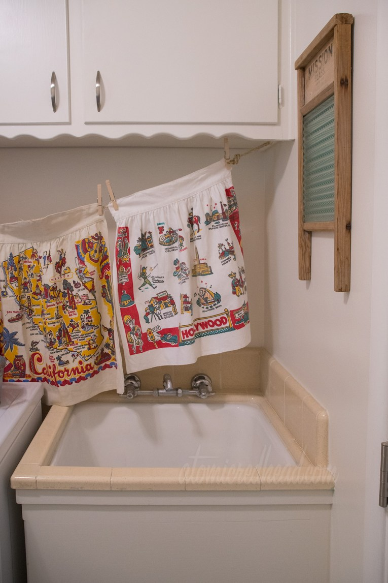A built in sink with cream colored tile offers a place for hand washing. Hanging above an apron of Hollywood, and on the wall a vintage washboard.