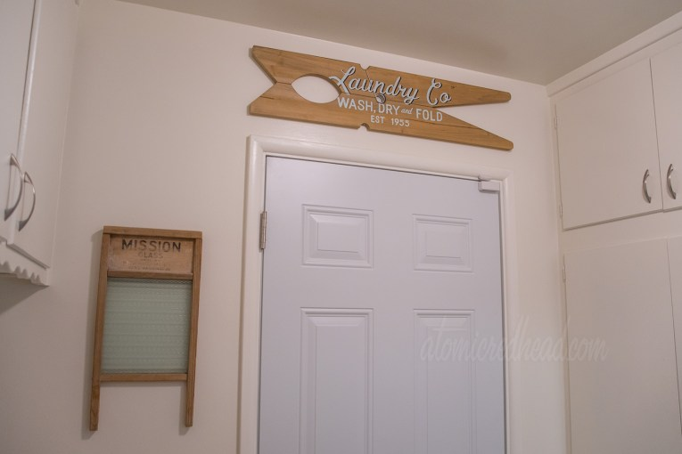 """To the left a vintage washboard hangs on the wall, above the door a large clothes pin shaped sign reads """"Laundry Co Wash Dry Fold Est. 1955"""""""