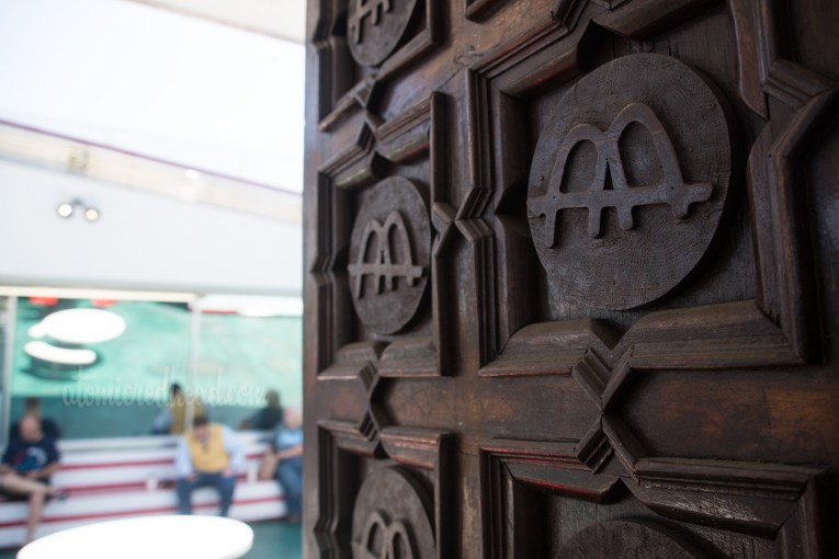 The doors to the museum, dark wood with carvings of the Golden Arches logo.