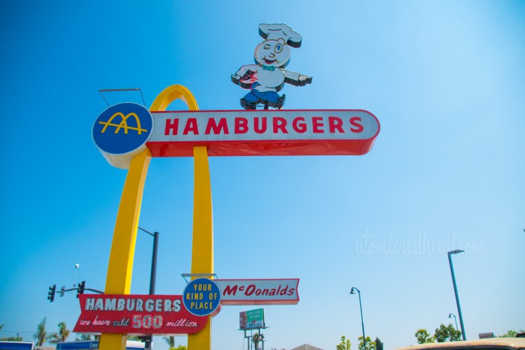 "The tall Speedee sign, a single golden arch stretches toward the sky, with a portion jutting out near the top reading ""Hamburgers"" Speedee, the hamburger faced chef points below. On the lower portion a red, blue, and white sign reads ""McDonald's Your Kind of Place"" and ""Hamburgers We have sold 500 million"""