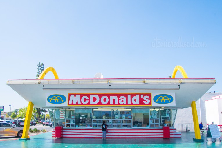 The building - two tall golden arches flank a slanted flat roof, and red and white tile wrap around the bottom. Walls of glass allow guests to walk up to the window and place their orders.