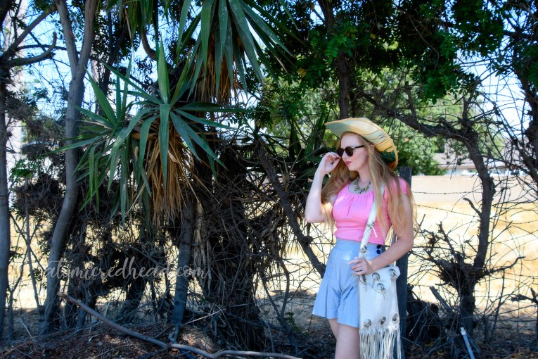 Hanging out in the shade of some trees, wearing a straw cowboy hat that features images of cacti, a pink peasant top, and blue and white stripe shorts. A white fringe leather purse on my shoulder, and a necklace featuring little cacti.