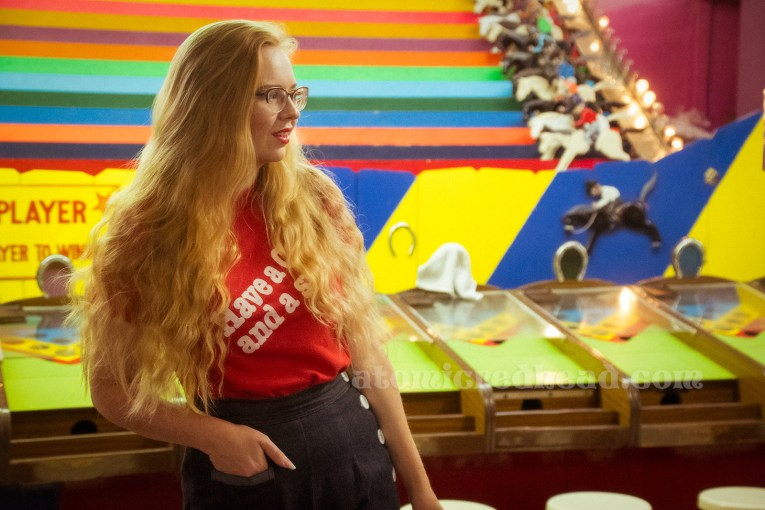 """Inside the Redondo Fun Factory - wearing a vintage red shirt reading """"Have a Coke and a smile"""" and wide leg blue jeans. In the background the multi-color horse trot game."""