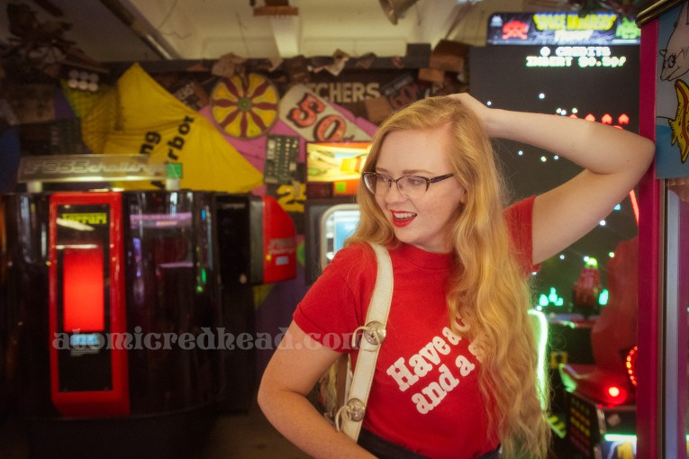 "Inside the Redondo Fun Factory - wearing a vintage red shirt reading ""Have a Coke and a smile"" and wide leg blue jeans. In the background a variety of arcade games and bizarre signs hang on the wall and from above."