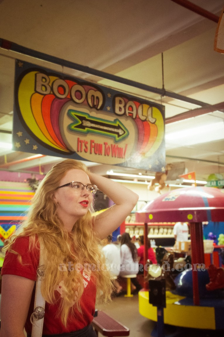 """Inside the Redondo Fun Factory - wearing a vintage red shirt reading """"Have a Coke and a smile"""" and wide leg blue jeans. Hanging from above a large sign reading """"Boom Ball"""""""