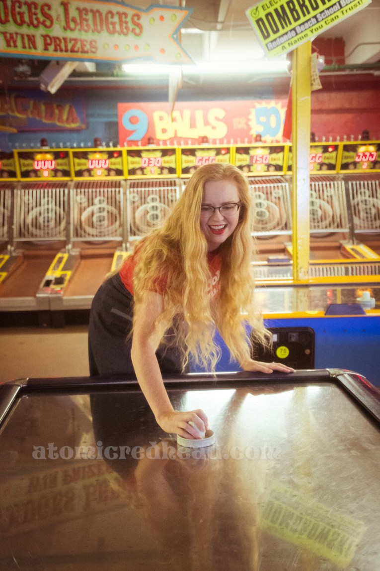 Playing air hockey, a wall of skee ball behind.