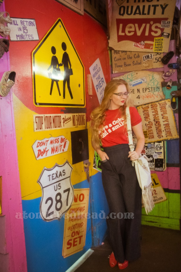 """Inside the Redondo Fun Factory - wearing a vintage red shirt reading """"Have a Coke and a smile"""" and wide leg blue jeans. A variety of signs, including a Texas highway sign, a school crosswalk sign, and more."""