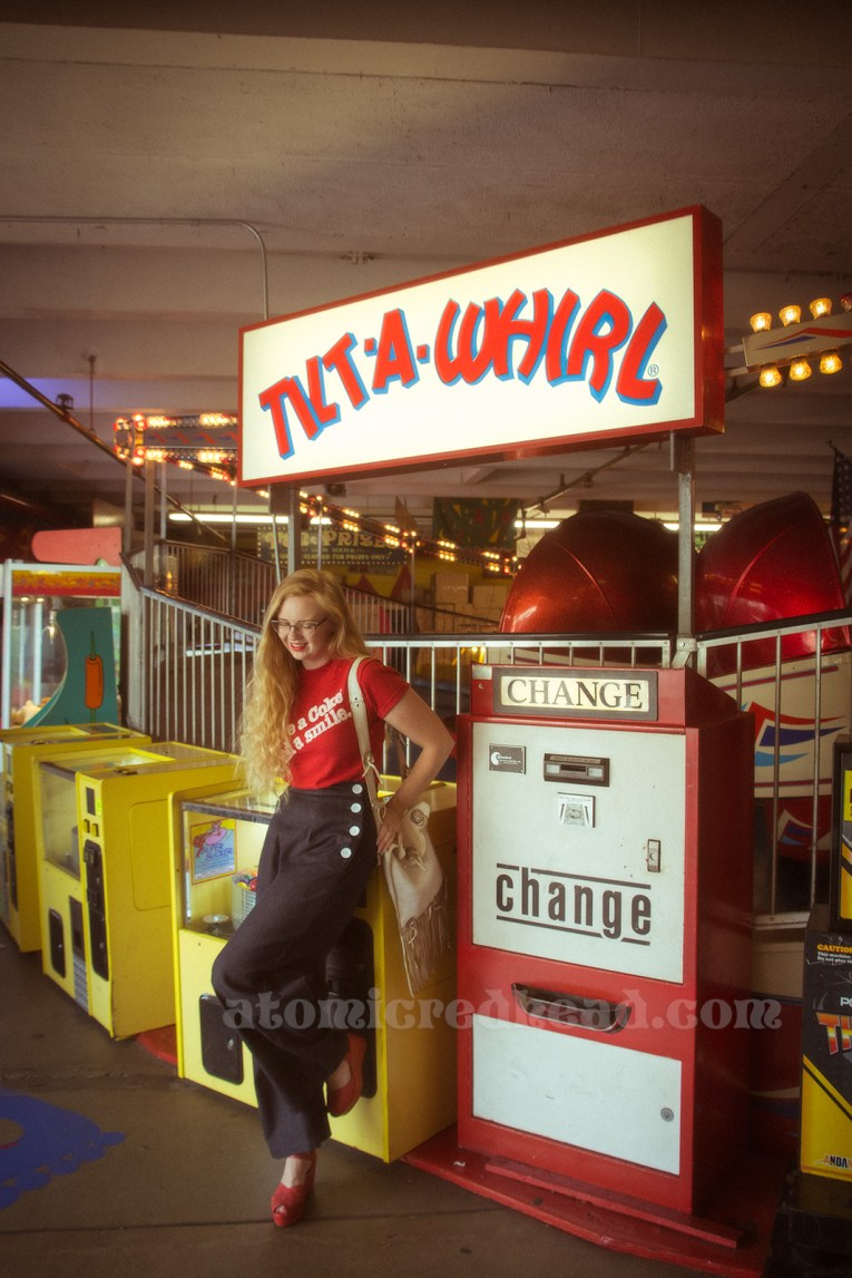 """Inside the Redondo Fun Factory - wearing a vintage red shirt reading """"Have a Coke and a smile"""" and wide leg blue jeans. Leaning against the Tilt-a-Whirl."""
