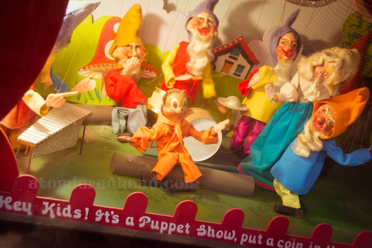 A mechanized puppet show with a blonde princess type dancing in the forest with animals and dwarves.
