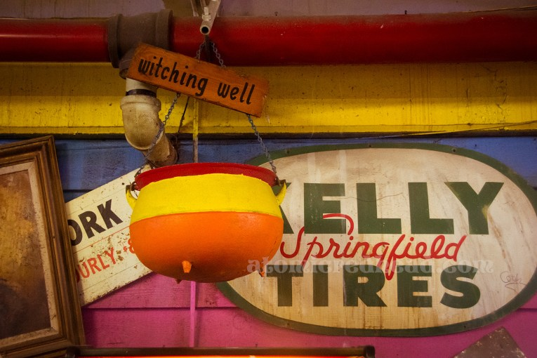 """A red, yellow, and orange painted cauldron hangs above, a sign reading """"Witching Well"""" is attached."""