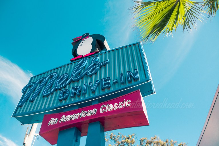 """A dapper penguin sits atop a blue neon sign reading """"Mel's Drive-In An American Classic"""""""
