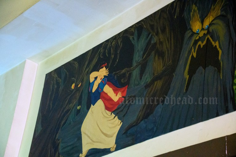 Mural of Snow White running scared from the terrifying trees with faces.