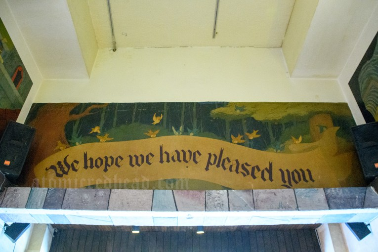 "Above the door, a mural of birds an the scroll reading ""We hope we have pleased you."""