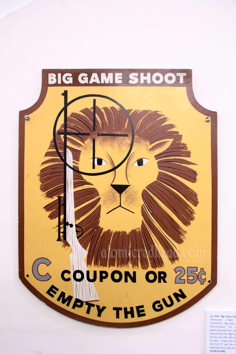 """Sign from the """"Big Game Shoot"""" shooting gallery that was in Adventureland, and features a lion and gun. Also reads """"C Coupon or 25 cents Empty the Gun"""""""