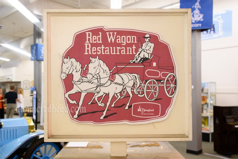 Signage for the Red Wagon Restaurant, featuring an illustration of a gentleman in a hose drawn red wagon.