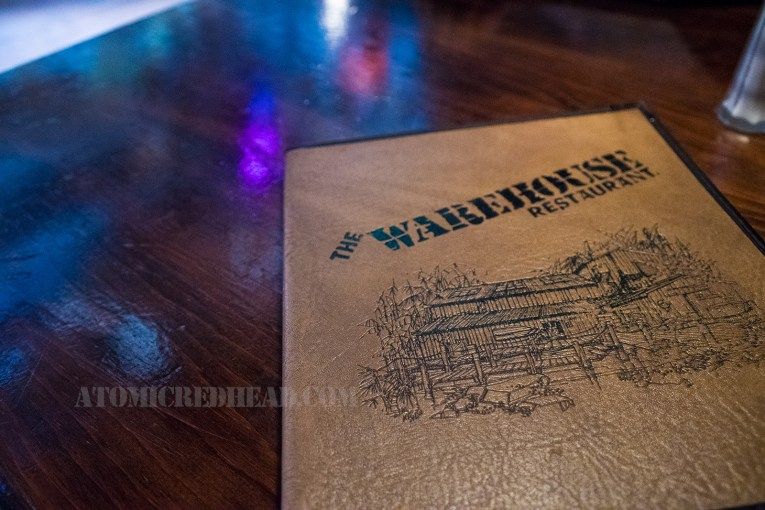 """The menu for The Warehouse, a tan faux leather, embossed with black, text reading """"The Warehouse"""" and an illustration of the front of the building."""