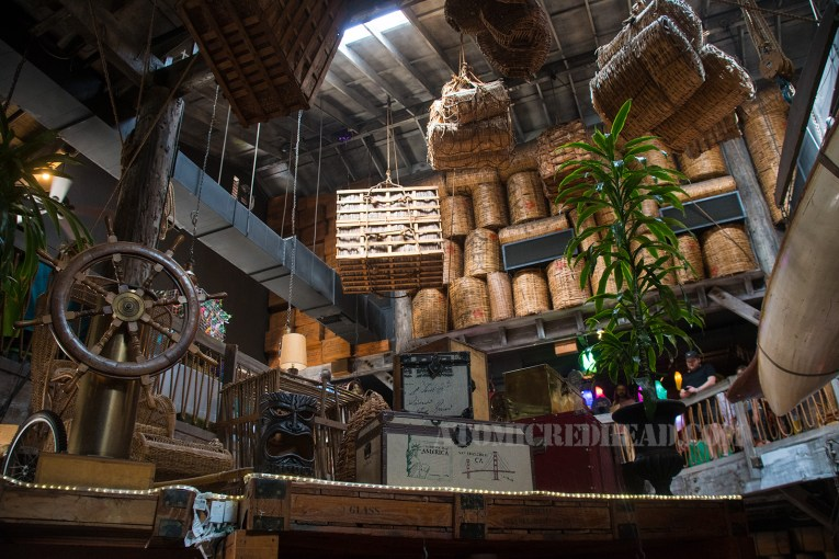 Large wooden crates that now house half circle booths stand in the middle, a ship's wheel atop one, several suitcases, crates, and tikis also sit atop. Large whicker baskets line the wall, and other crates and barrels hang from above, some sit in large nets.