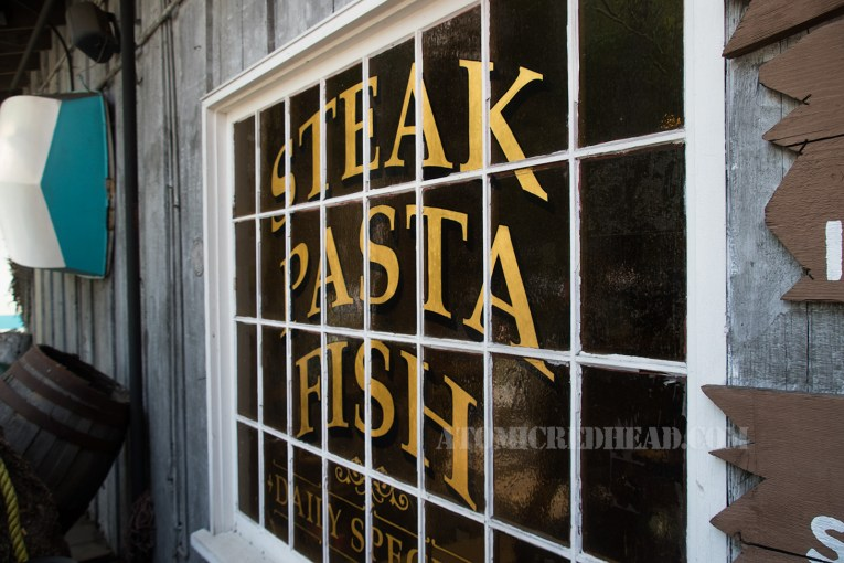 """The window outside reads """"Steak Pasta Fish"""" in gold letters."""