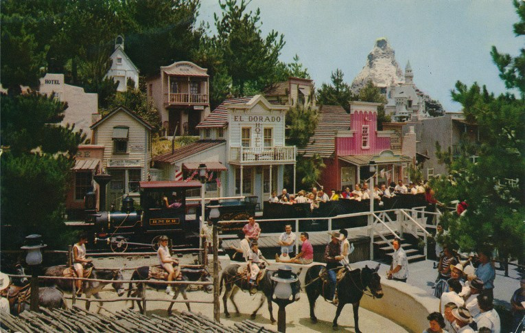 Small western buildings stand in the distance, in the foreground guests ride donkeys.