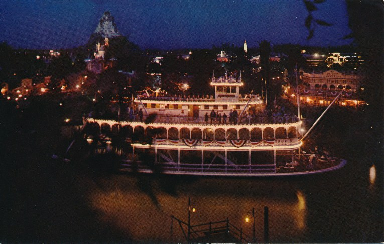 The Mark Twain at the dock at night, it is lit with hundreds of little white lights.