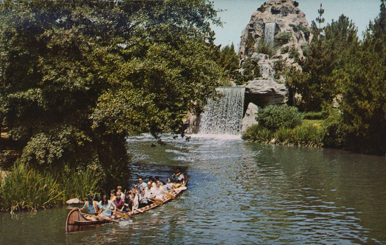 Guests paddle in a canoe past a waterfall.