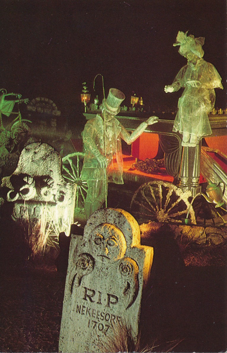 Inside the Haunted Mansion - tombstones sit upright, two ghosts talk near a horse-drawn hearse.