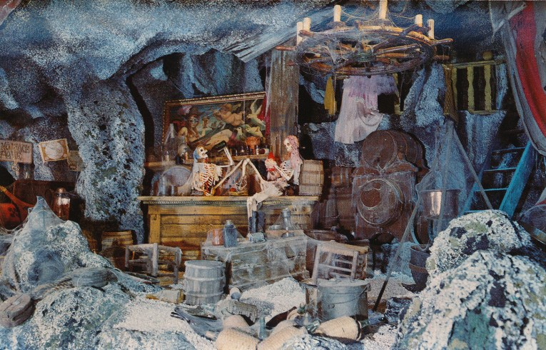 Interior of Pirates - two pirate skeletons hold bottles at a bar covered in cobwebs, a painting a female pirate hangs above the bar.