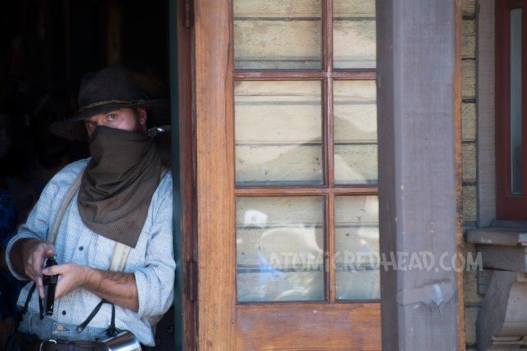 Tiny Mayfield, leans against a doorway to prepare to rob the bank. His kerchief on his face and gun in hand.