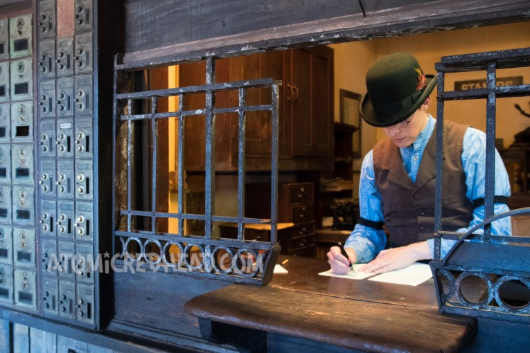 Levi stands behind the desk at the post office transcribing telegraphs as they come in.