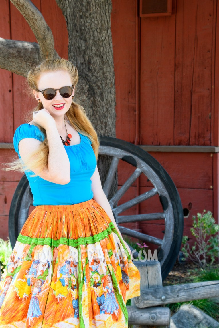 My outfit for the finale, a blue peasant top, and skirt of orange, red, yellow, and green which features an illustration of a barn dance.