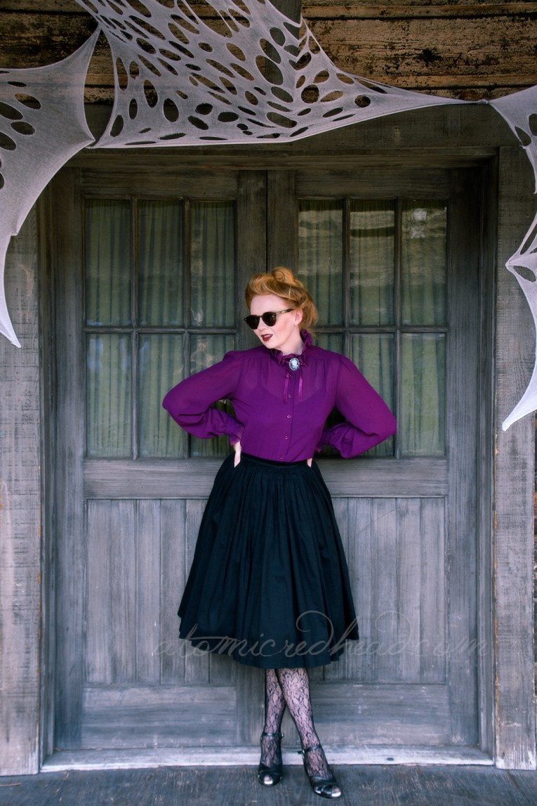 A pair of faded old wood doors with glass panels and pale green curtains in the background, myself standing in front, wearing a long sleeve purple, Victorian style shirt, with a black and white cameo, and a black full skirt, net style tights with a floral design and black shoes. My hair is piled atop my head in a Gibson Girl style.