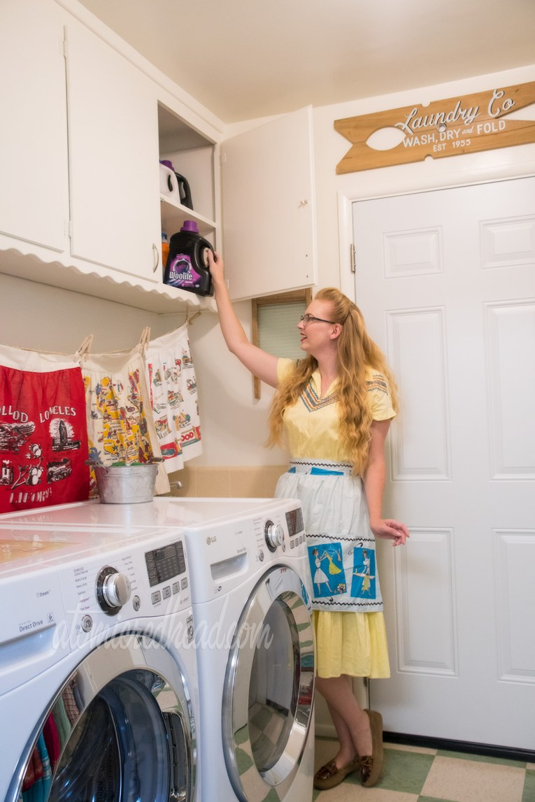 Me, standing in the laundry room reaching for a bottle of detergent, wearing a yellow dress with blue trim, and a blue and white apron featuring images of a woman doing laundry.