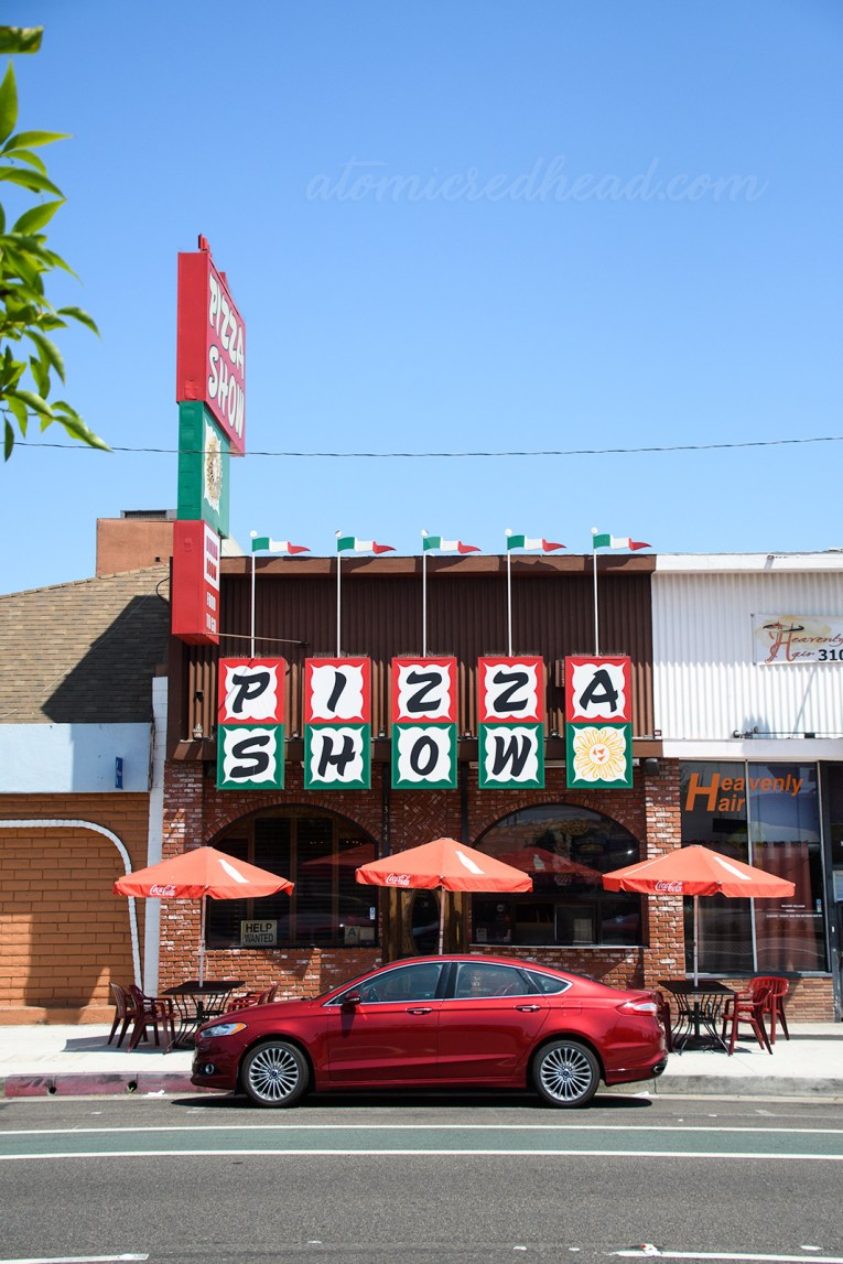 "Exterior of Pizza Show. Squares spell out ""Pizza Show"" with ""Pizza"" edged in red, and ""Show"" edged in green."