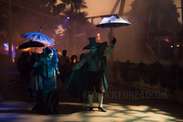 A crowd in gothic inspired fashion walk, some carrying parasols.