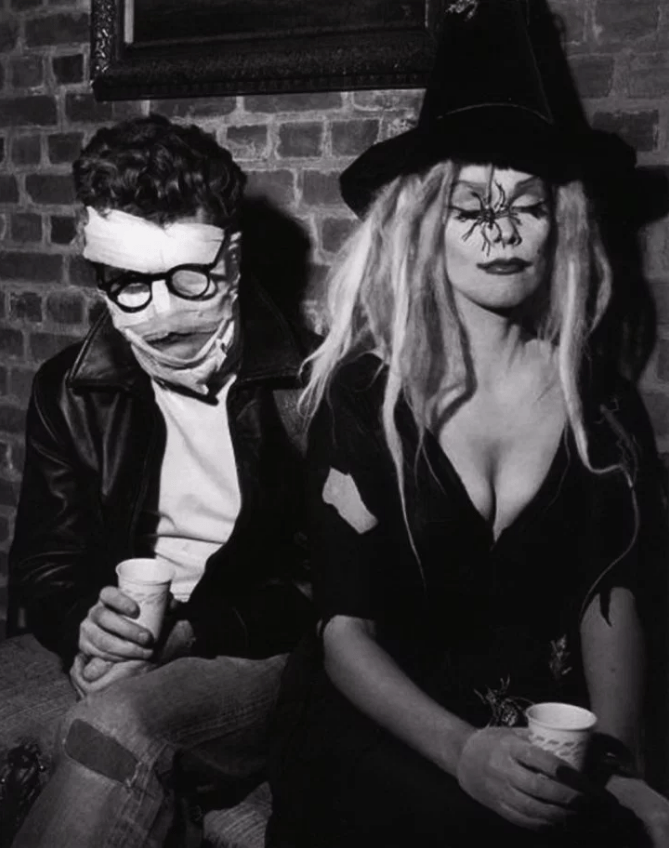 Jack Simmons, face wrapped in bandage, glasses, wearing a leather jacket. Nurmi in a black dress with plunging neckline, and witch hat with spider hanging down.