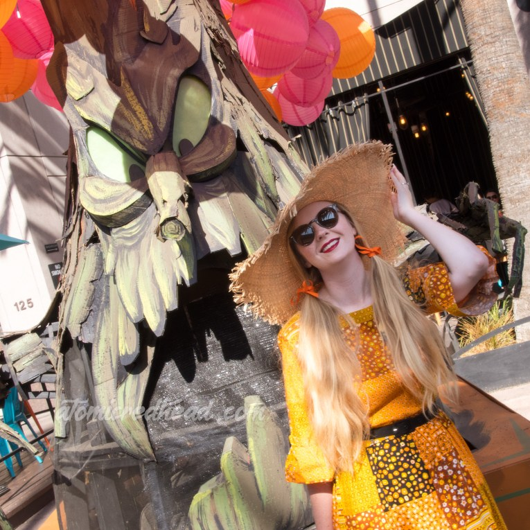 Myself standing in front of a spooky tree float, wearing a patchwork print dress of orange, yellow, black and white, as a large straw hat.