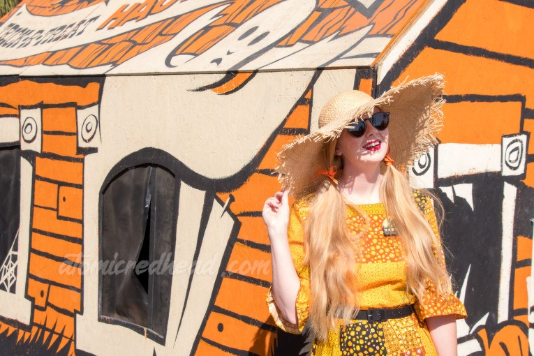 Myself standing in front of a float made to look like a vintage sucker box that also looks like a haunted house, wearing a patchwork print dress of orange, yellow, black and white, as a large straw hat