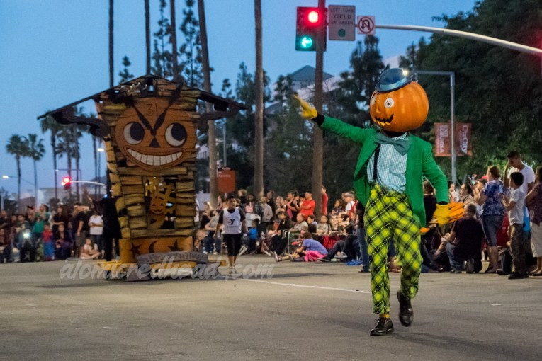 A parade performer wears a green and yellow costume and a large jack o'lantern head with a blue bowler on top.