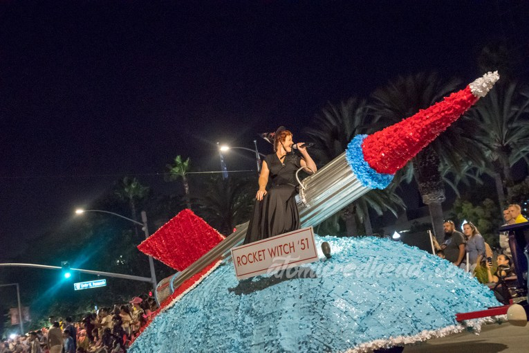 """A large silver and red rocket float with the """"Rocket Witch"""" sitting atop, wearing a black dress and black witch hat."""
