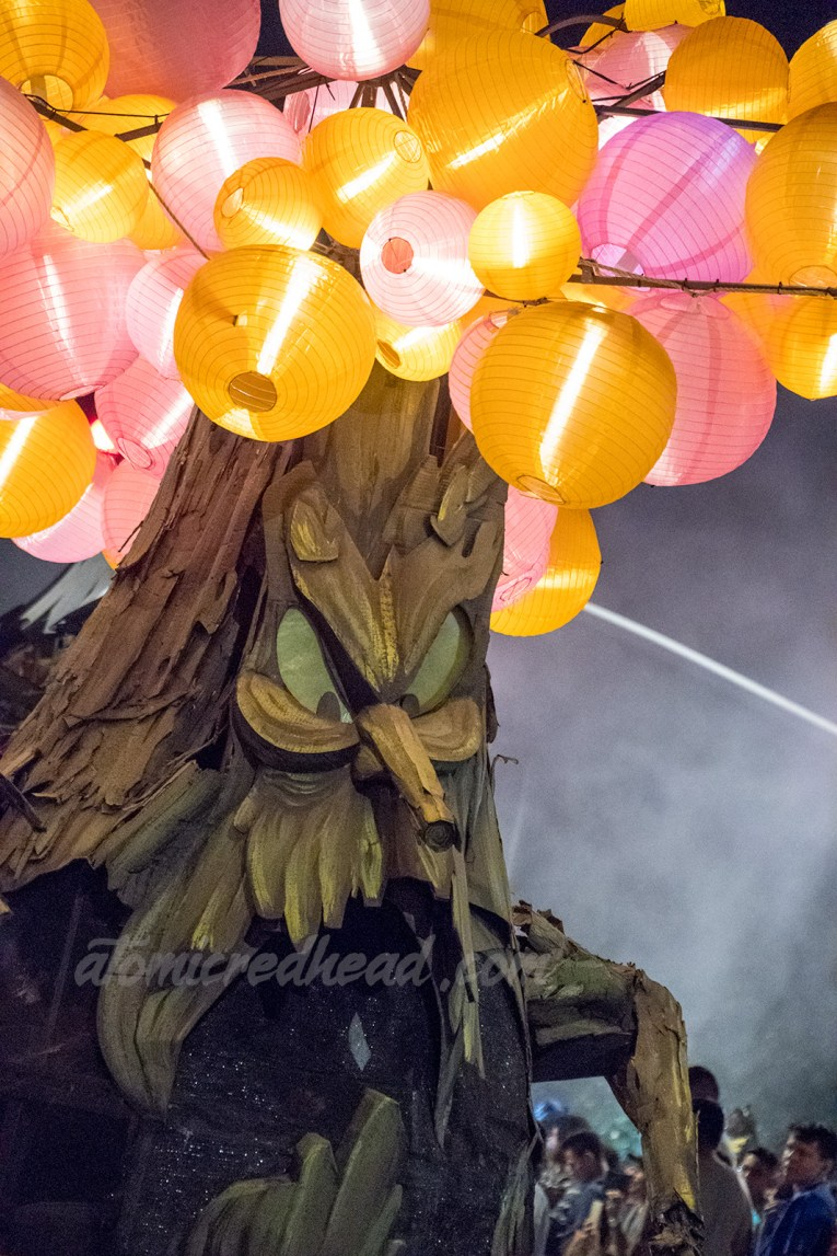 A spooky tree with a face and pink and orange lanterns hanging from its branches.