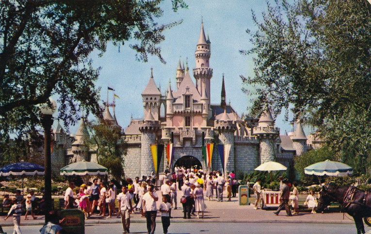 Sleeping Beauty's Castle, straight on. The walls have a pink tint to them, and greyish blue roofs. People mingle in front.
