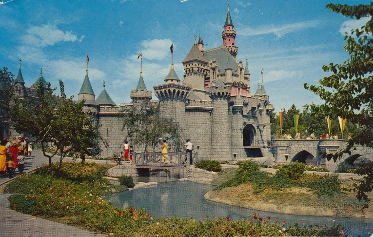 Sleeping Beauty's Castle, at an angle, Guests walk along a path near the moat and over the drawbridge.