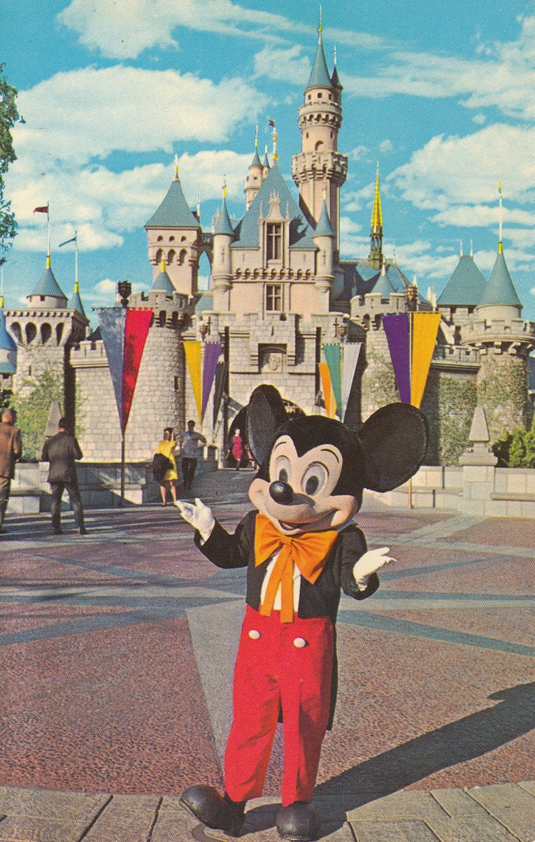 Mickey stands in front of Sleeping Beauty's Castle, which stands tall with white walls and pink roofs, brightly colored banners line the drawbridge.