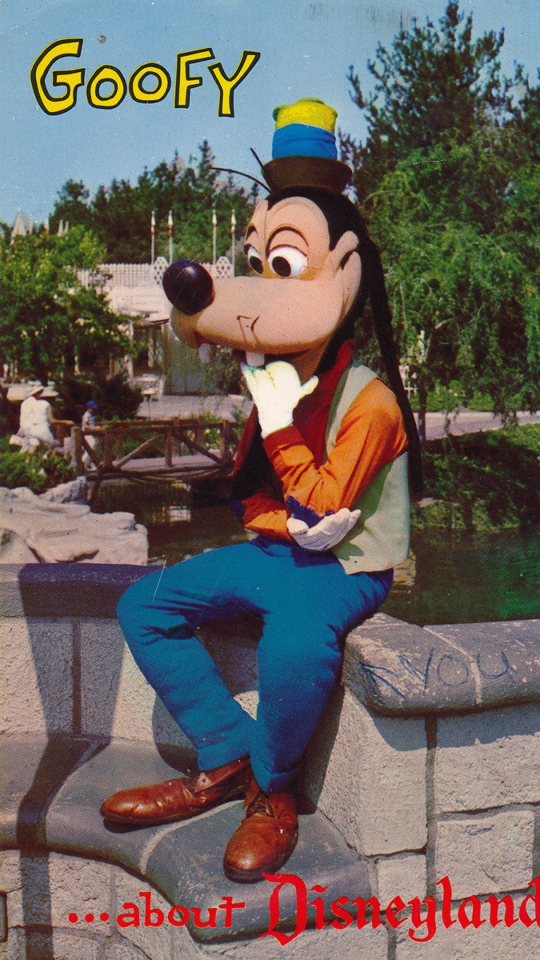 "Goofy sits on a wall near the castle, his hand in his mouth, text reads ""Goofy for Disneyland"""